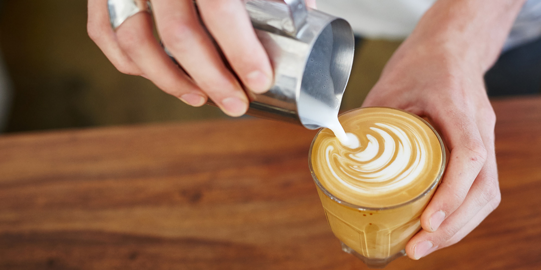 Pouring milk into a coffee latte